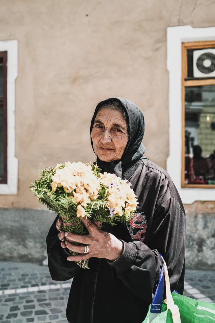Bettlerin mit Blumensträußen