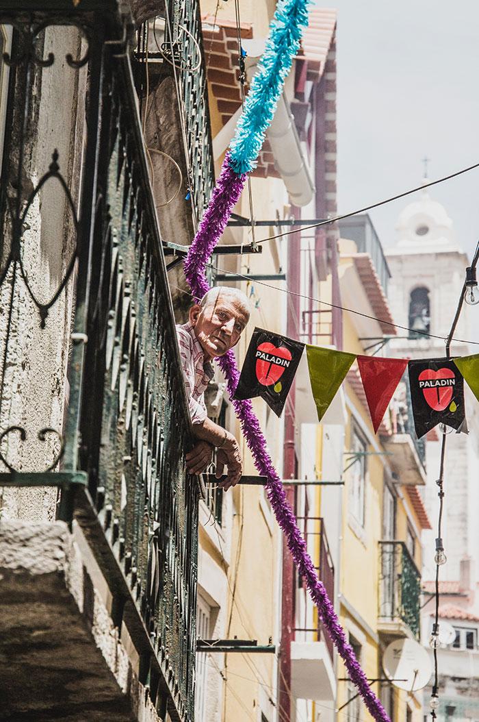 Mann auf Balkon Lissabon