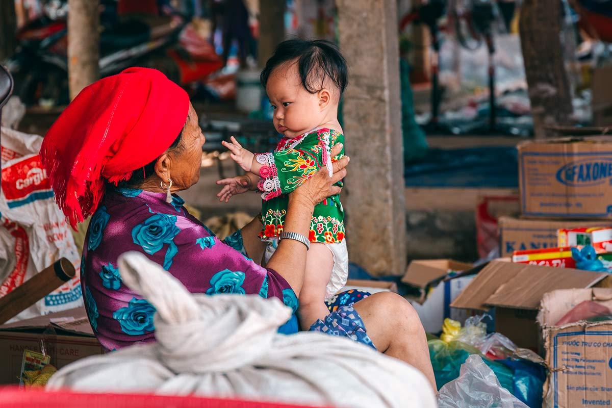 Alte Frau mit Kind auf dem Cho Coc Ly Markt