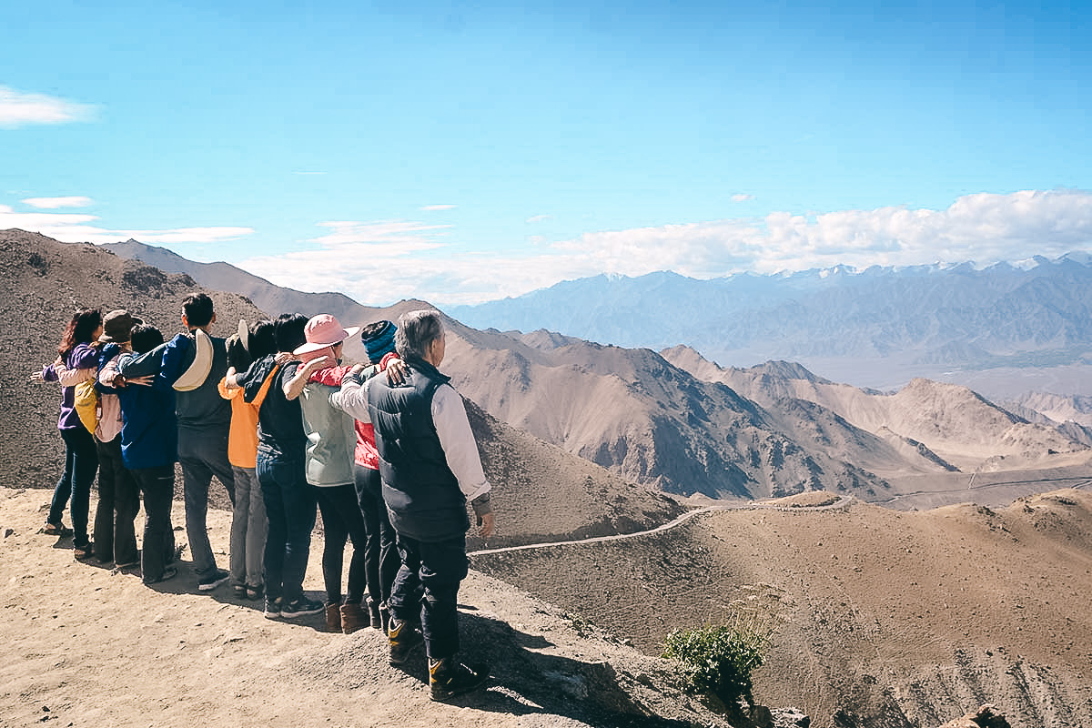 asiatische reisegruppe blickt auf dem weg ueber das himalaya ins nubra tal zurueck nach leh