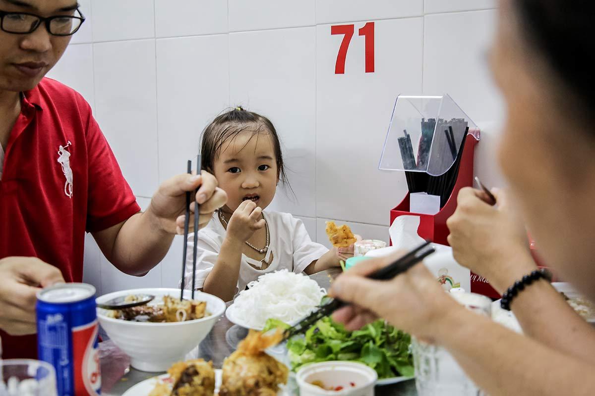 Maedchen isst Bun Cha im Bun Cha Huong Lien Restaurant in Hanoi