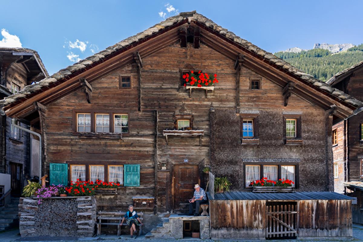 Vals in der Schweiz Aeltestes Haus am Dorfplatz in Vals mit Bewohnern